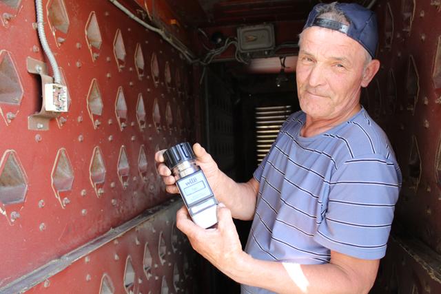 Оператор зерносушильной установки Виктор Бусел проверяет зерно на влажность.